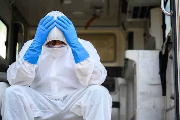 Profissionais de saúde que trabalham em ambulâncias de emergência usando roupas de proteção de epi. assistentes médicos sentam-se tristes e cansados na ambulância.