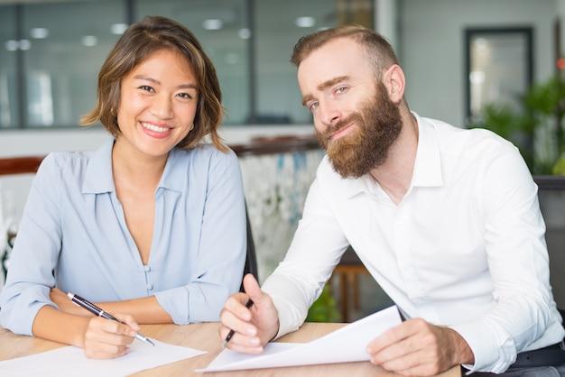 Profissionais de sucesso felizes estudando relatórios