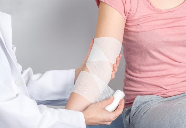 Profissional colocando uma bandagem de compressão para inflamação.