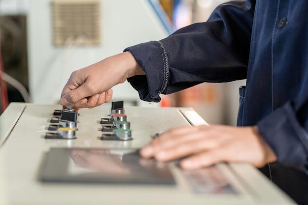 Profissional da planta industrial explicando a função da máquina cnc para trabalhador asiático na oficina