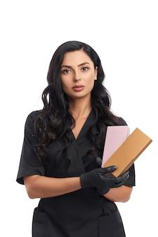 Profissional de beleza com uniforme médico preto e luvas segurando caixas com cosméticos
