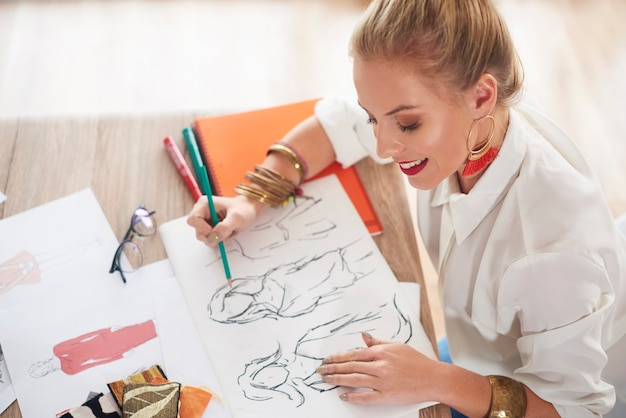 Profissional de design feminino desenhando à mesa
