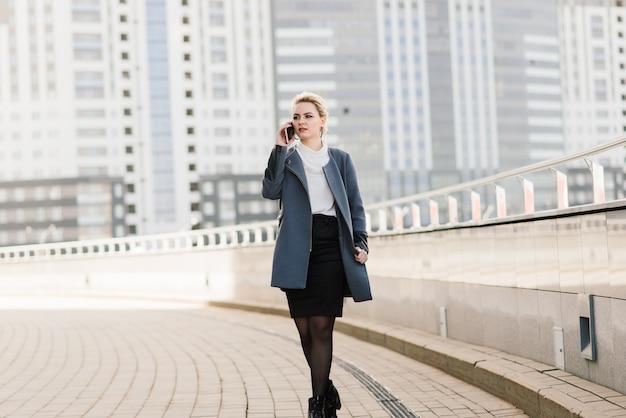 Profissional de empresária advogado caminhando ao ar livre falando no celular inteligente, bebendo café do copo de papel.