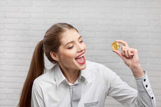 Profissional de finanças feminino positivo bonito olhando com emoção no bitcoin dourado