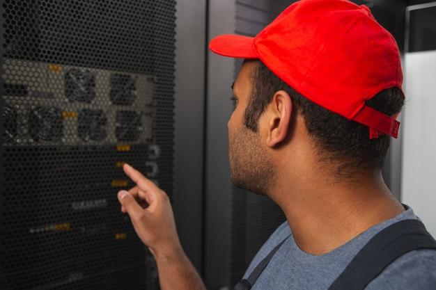 Profissional de informática. agradável engenheiro de ti voltando-se para o armário do servidor e apontando com o dedo