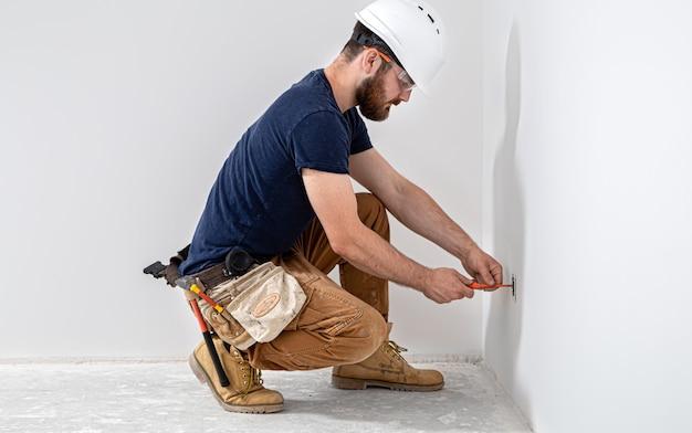 Profissional de macacão com ferramenta de eletricista na parede branca. reparo em casa e conceito de instalação elétrica.