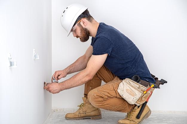 Profissional de macacão com ferramenta de eletricista no fundo branco da parede. reparo em casa e conceito de instalação elétrica.