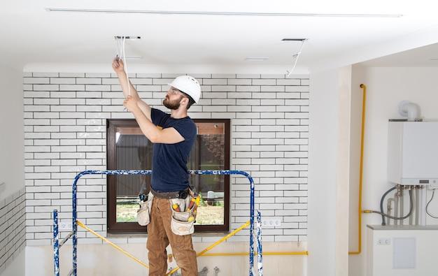 Profissional de macacão com ferramentas no fundo do canteiro de obras. conceito de renovação em casa.