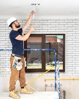 Profissional de macacão com ferramentas no fundo do canteiro de obras de corpo inteiro. conceito de renovação em casa.