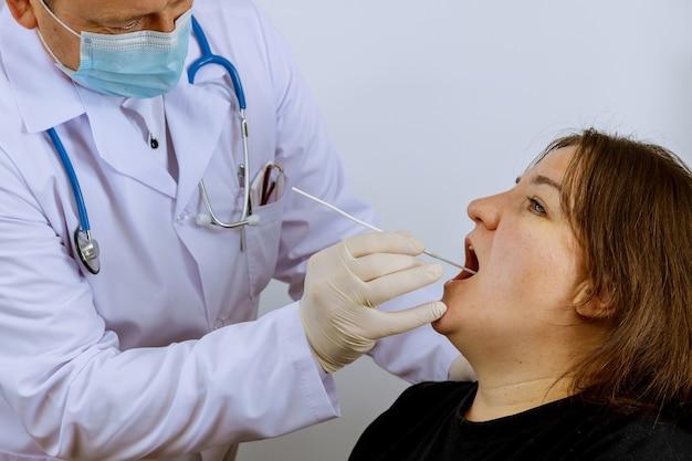 Profissional de saúde com equipamento realiza esfregaço de coronavírus em mulher em esfregaço bucal para coronavírus covid-19.