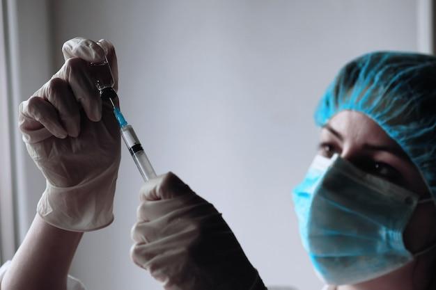 Profissional de saúde disca a vacina em uma seringa