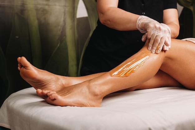 Profissional de spa fazendo uma sessão de adoçamento nas pernas para uma mulher encantadora