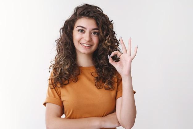 Profissional determinado, bonito, jovem funcionário armênio mostrar tarefa bem compreendida gesto, fazer gesto correto sorrindo amplamente concordar acho que a roupa parece excelente, fundo branco de pé