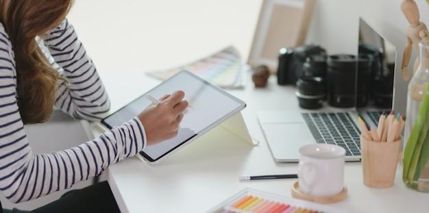 Profissional editando seu projeto com tablet no local de trabalho moderno
