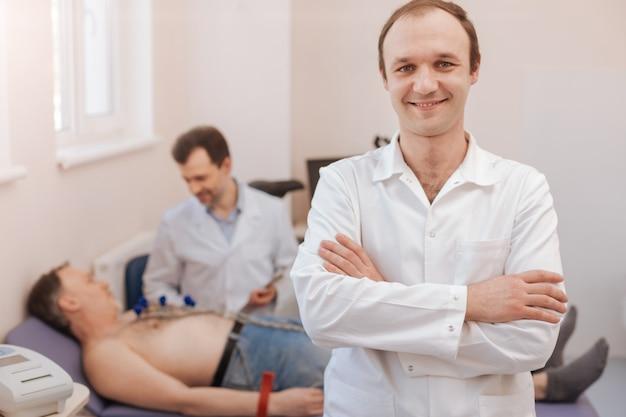 Profissional experiente inteligente regular pronto para executar alguns procedimentos de teste enquanto trabalha em equipe com seu colega que diagnostica seu paciente