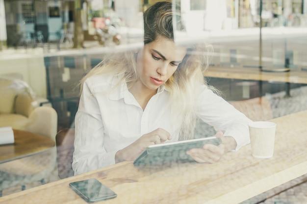 Profissional feminina concentrada sentada à mesa em um espaço de trabalho compartilhado ou café, usando um tablet