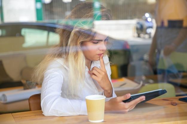Profissional feminina pensativa sentada à mesa em um espaço de trabalho compartilhado ou café, usando um tablet