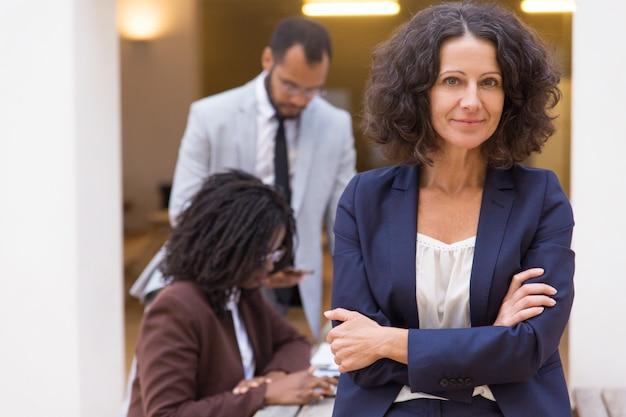 Profissional feminino bem sucedido amigável posando com os braços cruzados