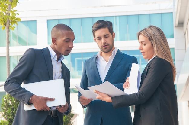 Profissional feminino, explicando os relatórios aos colegas do sexo masculino