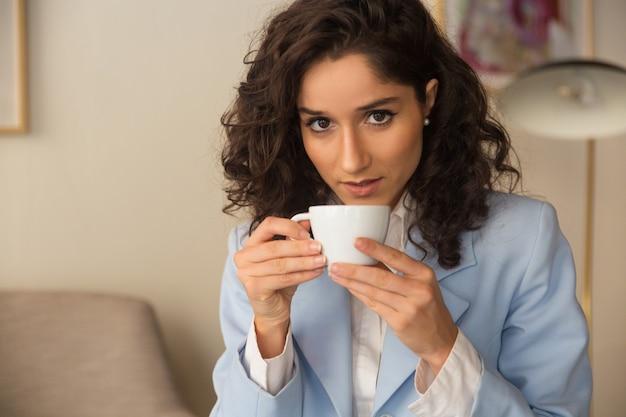 Profissional feminino pensativo, bebendo café em casa