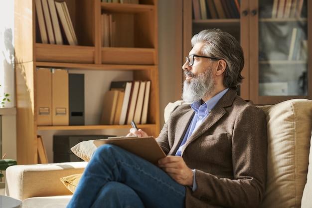 Profissional idoso sério, com cabelos grisalhos e barba, sentado no sofá em frente à janela e fazendo anotações no fundo das prateleiras com livros