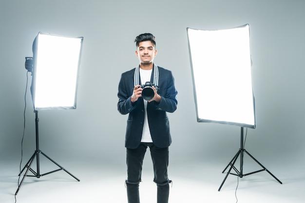 Profissional jovem fotógrafo indiano tirando fotos em estúdio com leight