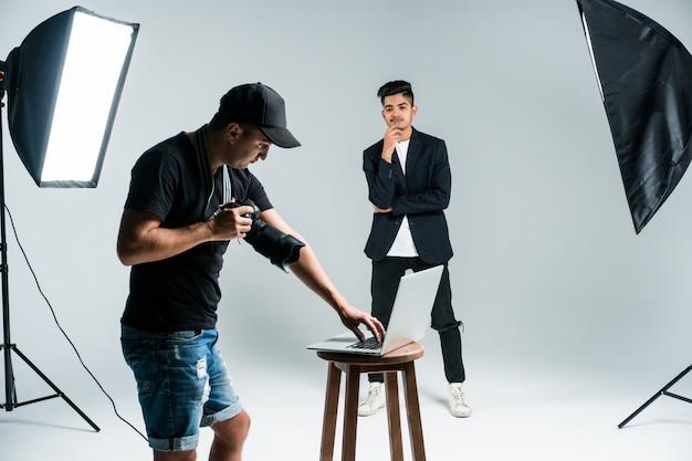 Profissional jovem fotógrafo tirando fotos de modelo indiano em estúdio com leight