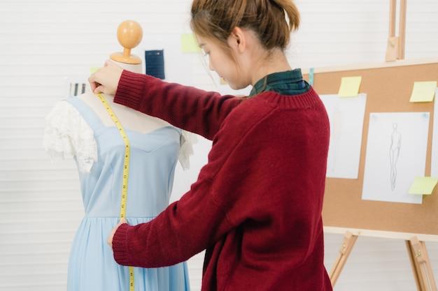 Profissional linda asiática feminino designer de moda trabalhando vestido de medição em uma roupa de manequim