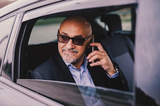 Profissional maduro elegante bem sucedido empresário está sendo conduzido no banco de trás do carro enquanto olha pela janela e fala em seu telefone.
