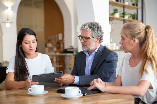 Profissional maduro explicando detalhes do contrato para clientes jovens