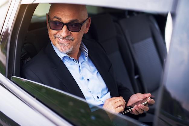 Profissional maduro feliz empresário bem sucedido está sendo conduzido no banco de trás do carro enquanto olha pela janela e usando seu telefone.