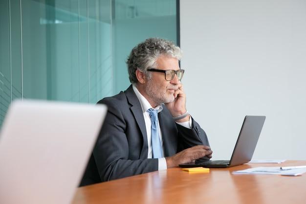 Profissional maduro sério de terno e óculos falando no celular, trabalhando no laptop no escritório, olhando para a tela