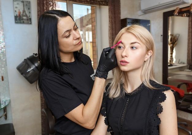 Profissional maquiagem artista sobrancelha tingimento com pincel no salão de beleza de garota atraente.