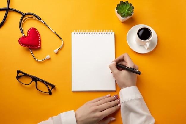 Profissional médico escrevendo registros médicos em um notebook com estetoscópio, xícara de café, seringa e coração
