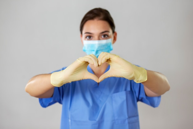Profissional médico forma o símbolo do amor com os dedos na frente dela.