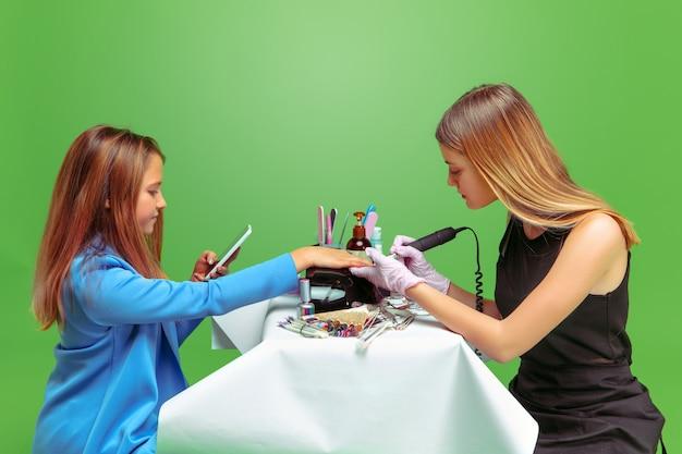 Profissional pintando as unhas de uma menina