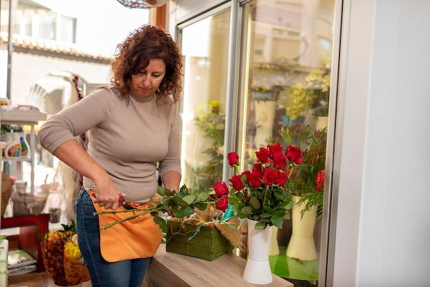 Profissional preparando buquê de rosas, com tesoura de poda