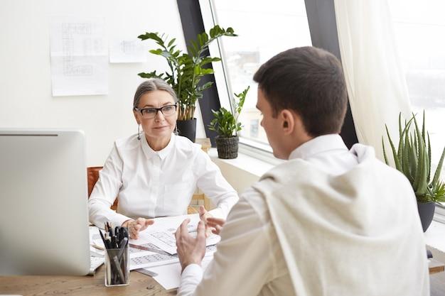 Profissional qualificada engenheira sênior em óculos, explicando algo para seu jovem estagiário. dois designers talentosos desenvolvendo design de interiores para projeto habitacional, discutindo plantas