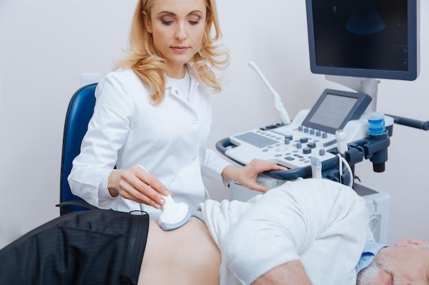 Profissional qualificado e útil concentrado que trabalha no hospital, enquanto fornece monitoramento ultrassônico do abdômen e usa máquina de ultrassom