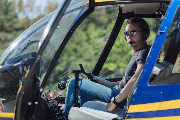 Profissional qualificado. jovem piloto atlético sentado em uma cabine piloto de um helicóptero e posando para a câmera, pronto para iniciar um vôo