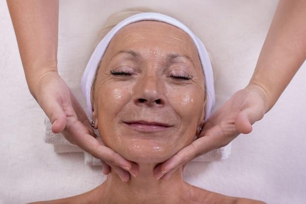 Profissional que cuida do rosto e da pele de uma mulher ender