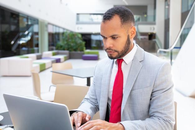 Profissional sério focado usando laptop e olhando para a tela