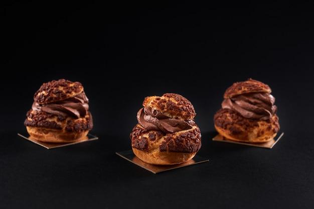 Profiteroles caseiros com creme de chocolate isolado no preto.