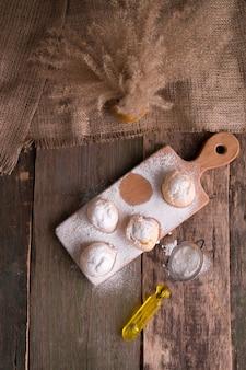 Profiteroles com açúcar de confeiteiro no fundo de madeira. estilo rústico.