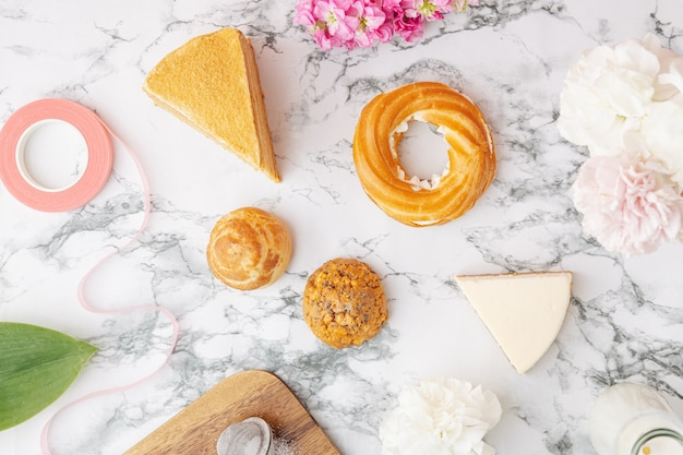 Profiteroles com creme, pedaço de bolo delicioso na mesa de mármore. doces sobremesas vista superior plana leigos. espaço para texto