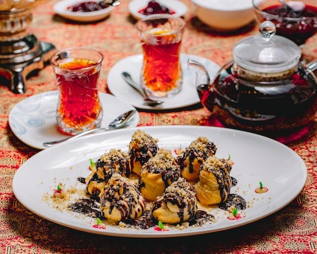 Profiteroles de sobremesa vista frontal com cobertura de chocolate e nozes raladas com dois copos de chá