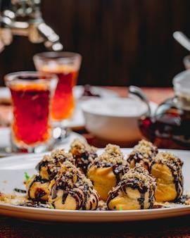 Profiteroles de sobremesa vista frontal com cobertura de chocolate e nozes raladas