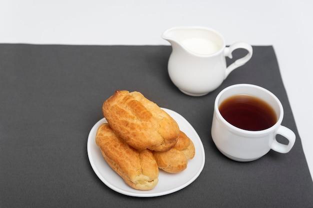 Profiteroles delicados caseiros na mesa, xícara de café. éclairs franceses tradicionais. vista do topo.