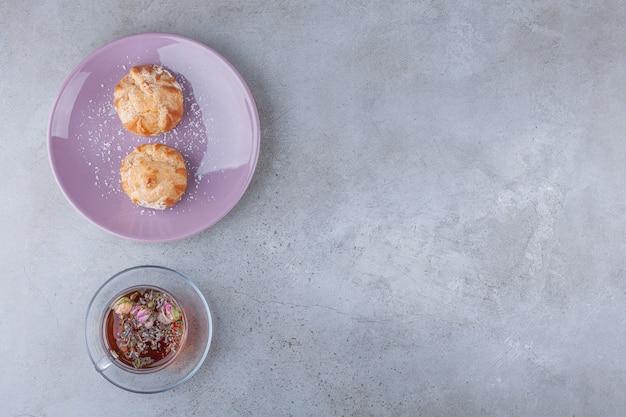 Profitroles de bolinhos pequenos com açúcar em pó e paus de canela.