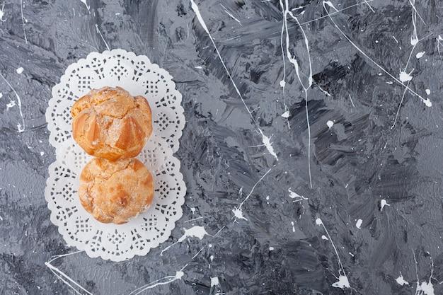 Profitroles de bolinhos pequenos com açúcar em pó.